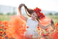Leuk meisje op de weide van rode papavers in de lentedag stock afbeelding