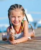 Leuk meisje op een houtvloer Stock Afbeelding