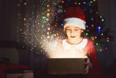 Leuk meisje op een Kerstmis/Nieuwe Year's-Vooravond die een heden openen royalty-vrije stock afbeelding