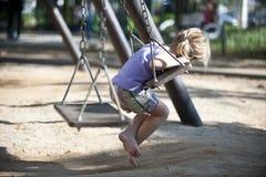 Leuk meisje op speelplaats het slingeren Royalty-vrije Stock Afbeeldingen