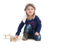 Leuk meisje in proefhoed met houten vliegtuig Stock Fotografie