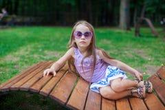 Leuk meisje in purpere glazen die op houten liggen stock afbeeldingen