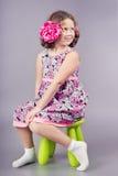 Leuk meisje in roze zitting op groene stoel Stock Foto
