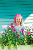 Leuk meisje in tuin op een achtergrond van turkooise omheining Stock Fotografie