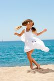 Leuk meisje in witte kleding die op strand danst. Stock Foto's