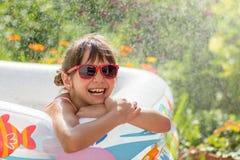 Leuk meisje in zonnebril vol in een opblaasbare pool Stock Fotografie