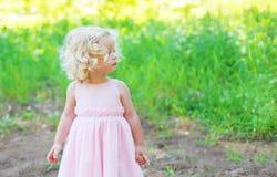 Leuk meisjekind met krullend haar die een roze kleding dragen Stock Foto