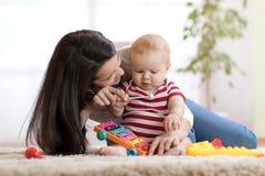 Leuk moeder en kindjongensspel samen binnen thuis stock afbeelding
