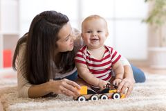 Leuk moeder en kindjongensspel samen met speelgoed binnen thuis royalty-vrije stock fotografie