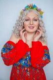 Leuk mollig meisje met bloemen in wit krullend haar in rode rustieke kleding royalty-vrije stock afbeelding