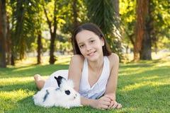 Leuk mooi glimlachend tienermeisje met witte en zwarte babyrabijn Stock Foto's