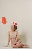 Leuk mooi meisje die rood ballonhart bekijken Stock Foto's