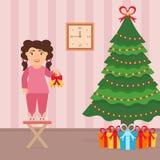 Leuk mooi meisje die zich op een stoel dichtbij de Kerstboom bevinden Stock Foto's