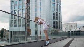 Leuk onbezorgd millenial hipstermeisje die pret en glimlach, stedelijke stadsstraten bij achtergrond hebben stock video
