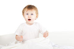 Leuk opgewekt babymeisje in bed thuis over wit royalty-vrije stock foto