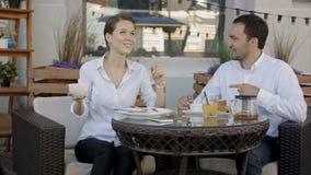 Leuk paar dat aan muziek samen in koffie op een zonnige dag in de stad luistert stock video
