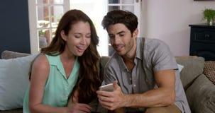 Leuk paar die elkaar hun smartphone tonen stock videobeelden