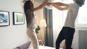 Leuk paar die hoofdkussen van strijd genieten die dan het koesteren op bed in lichte slaapkamer kussen stock footage
