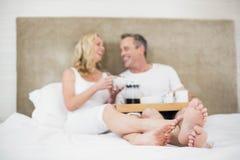 Leuk paar die ontbijt in bed hebben stock afbeelding