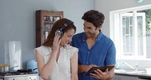 Leuk paar die tablet gebruiken terwijl het luisteren aan muziek stock videobeelden