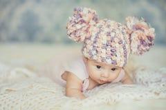 Leuk pasgeboren babymeisje in gebreid GLB met builen Stock Afbeelding