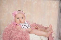 Leuk pasgeboren babymeisje, liggend op het bed, die camera bekijken Stock Foto