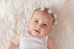 Leuk pasgeboren babymeisje, liggend op het bed, die camera bekijken Stock Fotografie