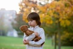 Leuk peuterkind, jongen, die weinig bruine teddybeer in Th houden Stock Fotografie