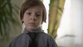 Leuk portret van weinig ernstige jongen met avondkleding op zijn hals die zich voor het venster met zijn wapens achter bevinden stock video