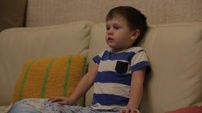Leuk portret van weinig jongenszitting op bank die op TV en het glimlachen letten Close-up stock videobeelden
