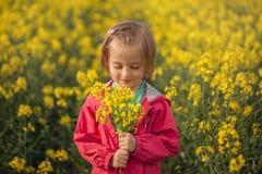 Leuk portret weinig jong geitje met bloemboeket op geel gebied in de zomer royalty-vrije stock fotografie