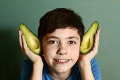 Leuk preteen jongen die elf met de avocadohelft uitvoeren stock foto