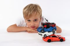 Leuk preteen jongen het liggen met een stapel van autospeelgoed en het maken van een verwarde blik in zijn gezicht stock afbeelding