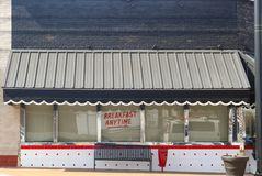 Leuk retro diner die met luifel met kammosselen boven venster op verkeer wijzen en om het even wanneer getoond Ontbijt stock fotografie