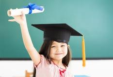 leuk schoolmeisje met graduatiehoed in klaslokaal stock foto's