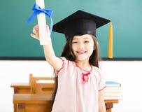 leuk schoolmeisje met graduatiehoed in klaslokaal royalty-vrije stock foto's
