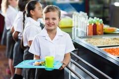 Leuk schoolmeisje met klasgenoot status dichtbij kantineteller royalty-vrije stock afbeelding