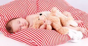 Leuk slapen weinig baby op rood en wit strepenhoofdkussen Royalty-vrije Stock Afbeeldingen