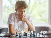 Leuk, slim, zit 11 jaar oude jongens in wit overhemd in het klaslokaal en speelt schaak op het schaakbord Opleiding, les, hobby, royalty-vrije stock foto's