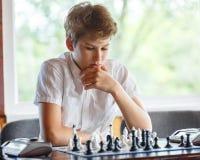 Leuk, slim, zit 11 jaar oude jongens in wit overhemd in het klaslokaal en speelt schaak op het schaakbord Opleiding, les, hobby royalty-vrije stock afbeeldingen