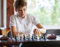 Leuk, slim, zit 11 jaar oude jongens in wit overhemd in het klaslokaal en speelt schaak op het schaakbord Opleiding, les, hobby stock foto's