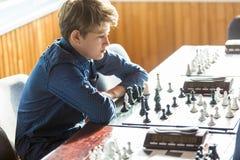 Leuk, slim, zit 11 jaar oude jongens in wit overhemd in het klaslokaal en speelt schaak op het schaakbord Opleiding, les, hobby, royalty-vrije stock foto