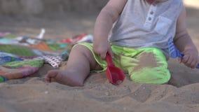 Leuk speelt weinig baby op het strand met peddel, hark en zand stock videobeelden