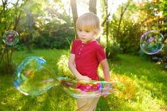 Leuk speelt weinig jongen met grote bellen openlucht Het kind blaast gelijktijdig grote en kleine bellen royalty-vrije stock foto