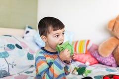 Leuk speelt weinig jongen met kleurrijke zachte groenten zittend op bed royalty-vrije stock afbeeldingen