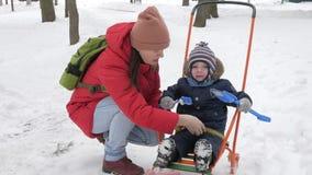 Leuk spelen weinig jongen en jonge moeder in de winter met sneeuw in het park Blauw jong geitje` s jasje en rood bij mamma stock footage