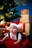 Leuk sprookjeportret van Kerstmis weinig baby die als de Kerstman bij de nieuwe jaarachtergrond onder boom dragen Stock Afbeeldingen