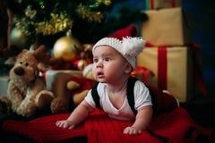 Leuk sprookjeportret van Kerstmis weinig baby die als de Kerstman bij de nieuwe jaarachtergrond onder boom dragen Stock Foto's