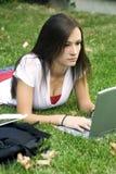 Leuk tienermeisje dat op het gras het bestuderen bepaalt Royalty-vrije Stock Fotografie