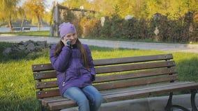 Leuk tienermeisje die en op de telefoon in de zitting van het de herfstpark op de bank glimlachen spreken Tand steunen Slow-motio stock video